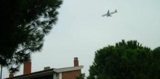 Avión sobrevolando por encima de las casas.