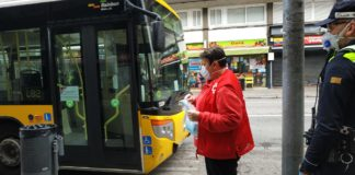 Una voluntaria de la Cruz Roja reparte mascarillas quirúrgicas en la parada del bus en Sta. Creu de Calafell. Foto: Ayuntamiento de Gavà.